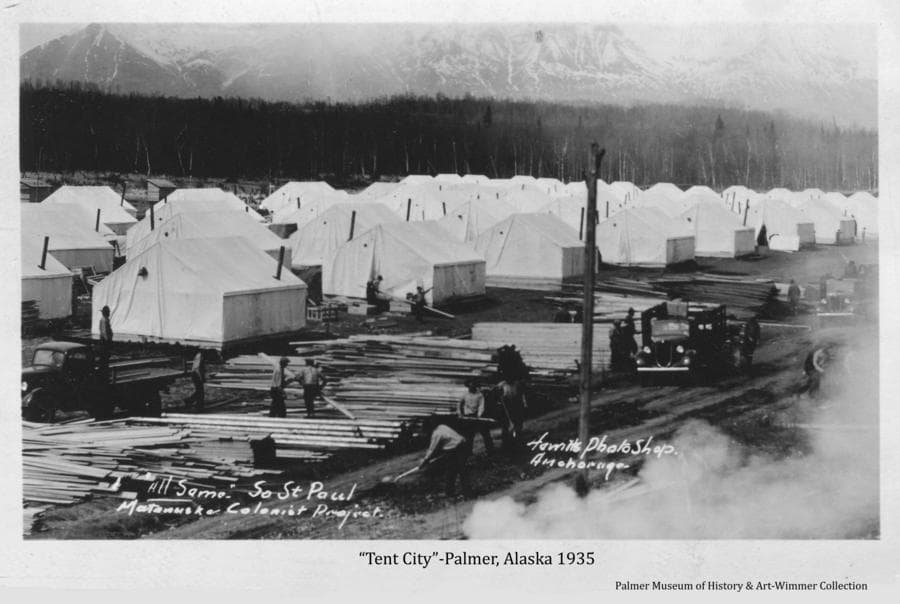 Image is of men loading lumber onto trucks from piles in front of many Colony tents at Palmer during the early days of the Colony project.
