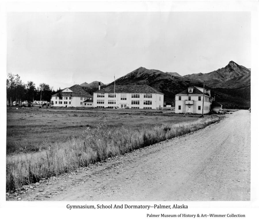 Image is of the west sides of the Community Gym, School and Dormitory.  The chicken coops are visible to the left of the gym.  Lazy Mt. and Buyer's Peak are in background.  Street in foreground later named E. Elmwood Ave.  A pickup is visible near the dorm and a truck is visible near the gym.