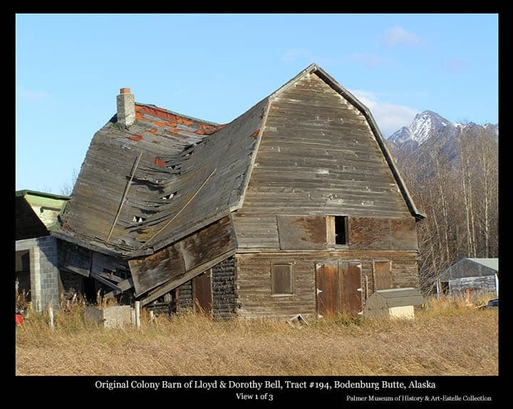 Image is a fall view of a Colony Barn, identified as located on Tract #194 near Bodenburg Butte, having originally belonged to Colonists Lloyd and Dorothy Bell.  The barn exhibits significance evidence of advanced stages of collapse.  Portions of other buildings are evident adjacent and nearby, Beyers Peak is in background.  This farm, located at the corner of Bodenburg Loop Road and Doc. McKinley Ave., was later owned by dentist Lee McKinley prior to the later demise of the barn.  This photo is number one of three documenting the collapse of this barn.