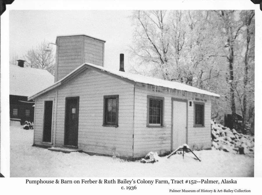 Image is a winter scene of a small white, single story building in foreground, identified as the pump house of Colonists Ferber & Ruth Bailey, located on Tract # 152.  A two-story hexagonal tower at the back of the pump house is identified as the water tank enclosure.  Part of the barn is visible behind the pump house at its original location before it was moved to make way for the highway construction cut straitening the Glen Highway up Bailey Hill.
