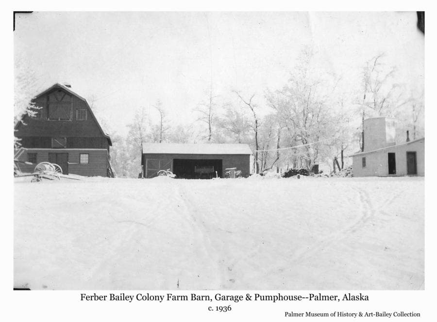 Image is a winter, easterly view, of the barn, garage and pump house of Colonists Ferber & Ruth Bailey, located on Tract # 152.  A two-story hexagonal tower at the back of the pump house is identified as the water tank enclosure.  The barn is at its original location before it was moved to make way for the highway construction cut straitening the Glen Highway up Bailey Hill.