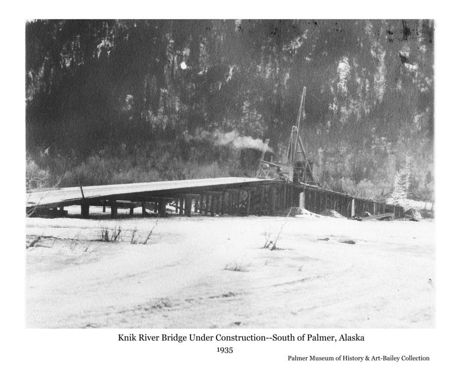 Image is a winter view of the Knik River Bridge under construction showing a derrick on the wooden platform ready to hoist steel girders into place.  Pioneer Peak mountainside is the backdrop.