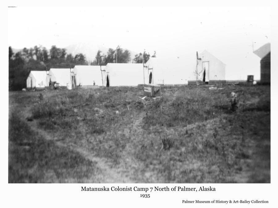 Image shows six white Colony tents in a row at Camp #7.   A small child stands in the path at right.  Camp 7 was located on Tract #157 drawn by Albert Fredericks along the Fishhook Road north of Palmer, Alaska.  This tract was located on what had apparently previously been part of a homestead with buildings and some land already cleared.