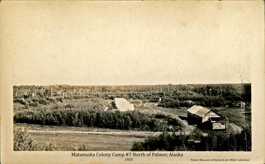 Image shows six white Colony tents in a row at Camp #7.   Camp 7 was located on Tract #157 drawn by Albert Fredericks along the Fishhook Road north of Palmer, Alaska.  This tract was located on what had apparently previously been part of a homestead with buildings and some land already cleared as apparent in this photo.