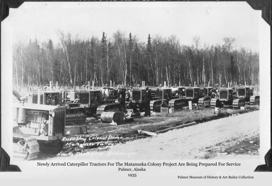 Image is of a number of Caterpillar tractors, newly arrived in Palmer for use associated with the Matanuska Colony Project.  Men are visible inspecting and servicing the tractors to get them ready to be put to work.