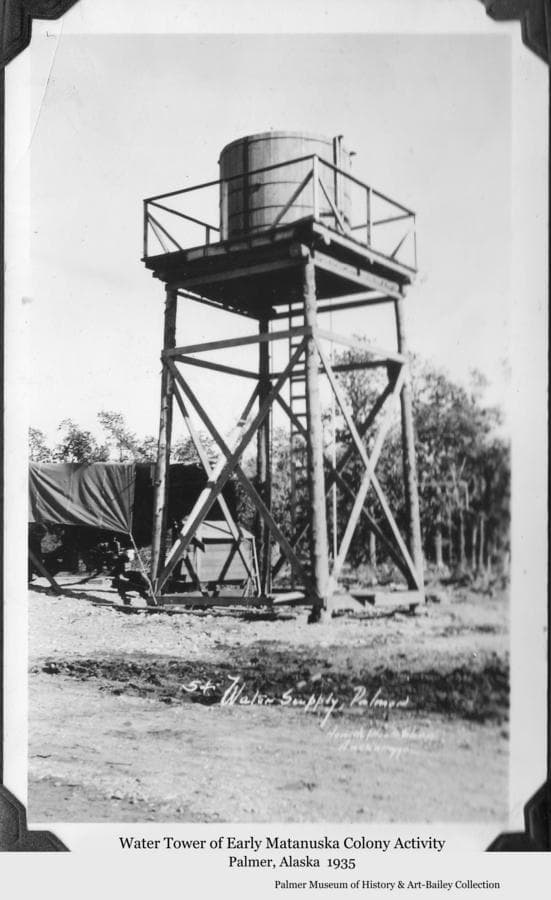 Image is of a water tank atop a four-legged pole tower to provide water under pressure to Matanuska Colony Project facilities in Palmer prior to construction of the permanent water tower in 1936.