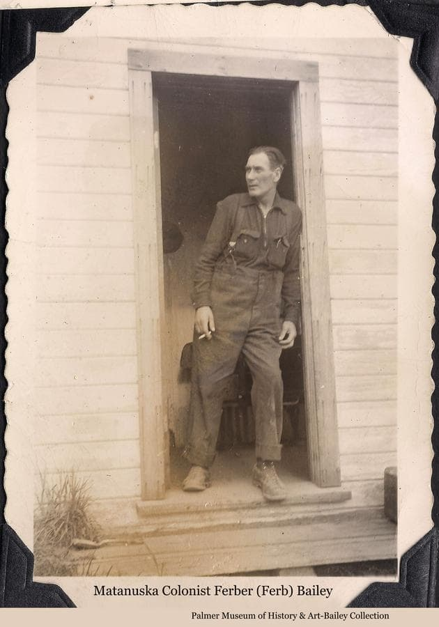 Image is of Colonist Ferber Bailey standing in the doorway of a house.