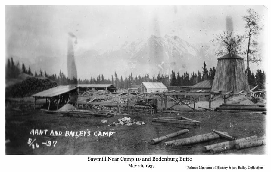 "Image is a summer view of a sawmill complex of buildings, logs, sawdust and scraps of wood, identified as ""Arnt and Bailey's Camp"".  Location is identified as near Bodenburg Butte and Camp 10.  A Caterpillar tractor is also visible."