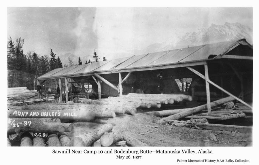 "Image is summer view of a sawmill, identified as ""Arnt and Bailey's Mill"", with a roof over the mill, and logs staged to be cut.   Location is identified as near Bodenburg Butte and Camp 10."