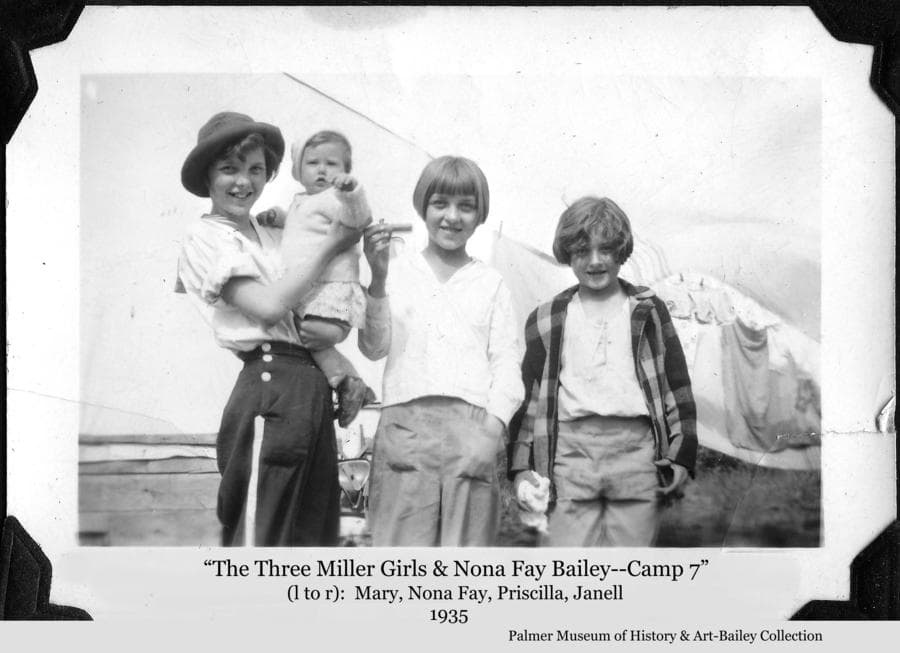 Image is a summer view of four girls, identified as Mary Miller holding baby Nona Fay Bailey, Priscilla Miller in center, and Janell Miller at right.  Nona Fay was the daughter of Colonists Ferber & Ruth Bailey.  The other three were daughters of Colonists Neil and Margaret Miller.  They are standing in front of one of the tents located at the temporary Colonist camp #7 north of Palmer, Alaska.