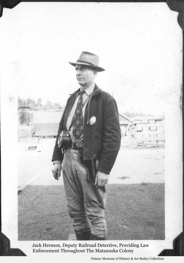 "Image is of a man, thought to be Colonist Jack Hermon, posing with his railroad detective badge, hand gun & night watchman's clock.  The family album containing this photo mistakenly identified the man as Don Irwin, Matanuska Colony manager.  Irwin, in his book concerning the Colony, ""The Colorful Matanuska Valley"", discusses theft problems connected with the project and identifies Hermon as the man appointed as Deputy Railroad Detective with authority to deal with law enforcement.  Irwin writes, ""Hermon was an ex-Marine and tough.  He could be found at most any hour checking on the camp and making his rounds in the warehouse and storage areas."""