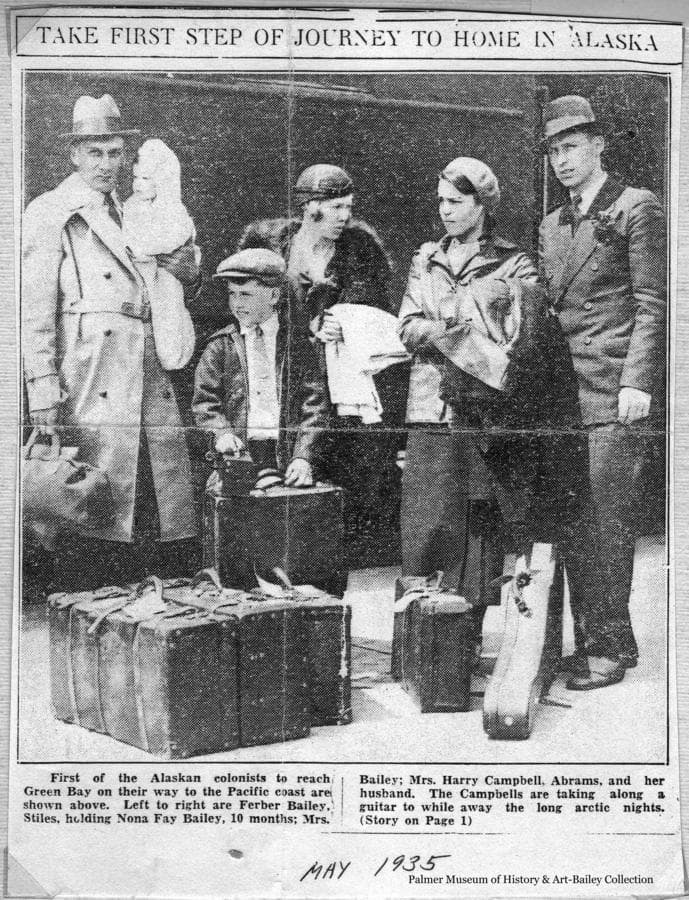 This is a press photo of two families selected to take part in the Matanuska Colony Project as they arrive at the Green Bay, Wisconsin train depot on their journey to Alaska.  They are identified as, left to right: Ferber Bailey holding his ten month old daughter, Nona Fay; Gene Bailey; and Ruth Bailey.  Theodora Campbell and husband, Harry Campbell are at right.