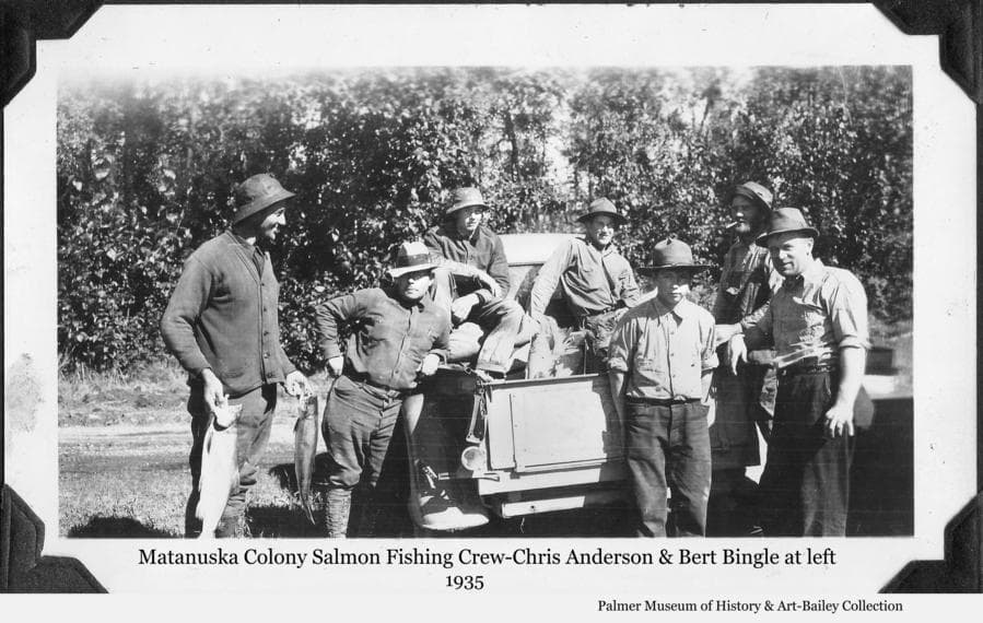 Image is a summer view of seven men gathered around the back of a pickup truck.   A man at left, identified as Colonist Chris Anderson, is holding two salmon in his hands.  Additional salmon are visible in the back of the truck.  Rev. Bert Bingle leans against the truck next to Anderson.