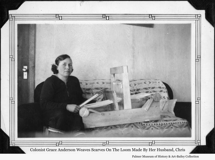 Image is of Colonist Grace Anderson sitting at her loom where she weaves scarves and other small items.  The loom was made for her by her husband, Chris Anderson.
