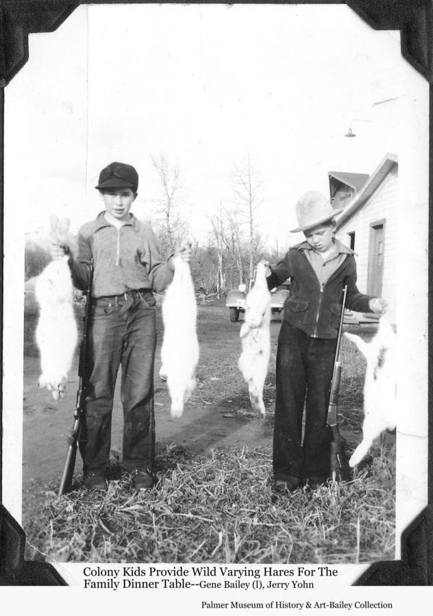 Image is of Colonist children Gene Bailey (left) and Jerry Yohn exhibiting snowshoe rabbits (varying hares) that their hunting will contribute to the family dinner tables.