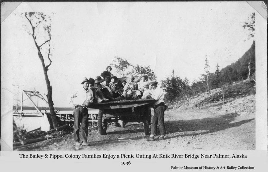 "Image is of the Bailey and Pippel families in the back of a truck with Walt Pippel and Ferb Bailey standing alongside.  They are identified as being on a picnic outing at the south end of the new Knik River Bridge south of Palmer.  This location apparently became a ""destination"" for many in the Palmer area shortly after the bridge opened in the fall of 1936.  Several collections in the museum from different sources contain photos of people and their automobiles here at the southerly approach to the bridge."