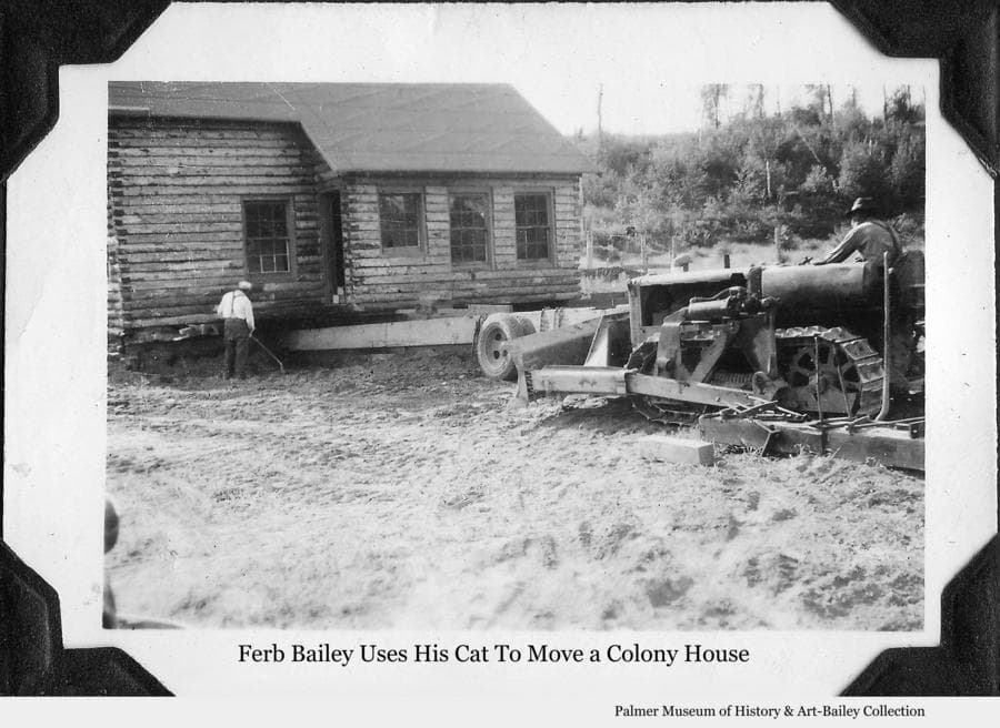 Image is of a log Colony house being readied to be moved.  One man, identified as colonist Ferber Bailey, operates a caterpillar tractor while an unidentified man assists in placing transport beams under the house.  Over the years since the Matanuska Colony houses were constructed in 1935, many have been moved from their original locations as farms were consolidated and as housing was needed in Palmer or elsewhere throughout the valley.