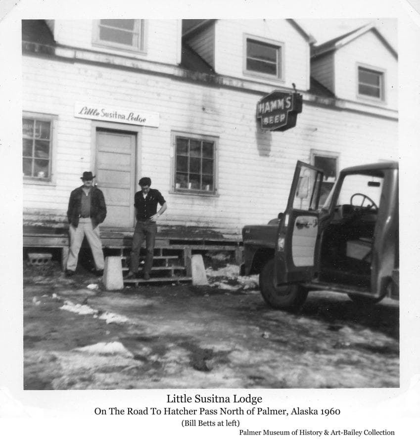 "Image is of a portion of a large white building, identified as the Little Susitna Lodge, with two men standing in front.  The man on the left is identified as Bill Betts.  A pickup truck is partially visible in front as well.  A ""Hamm's Beer"" sign is evident on the building wall.  This establishment, on the road to numerous gold mines in the mountains nearby, had a history of burning down several times and being re-built to operate under various business names including ""Little Su Roadhouse"", ""Fishhook Inn"", ""Little Susitna Lodge"" and ""Mother Load Lodge"".  It burned again April 17, 2015."