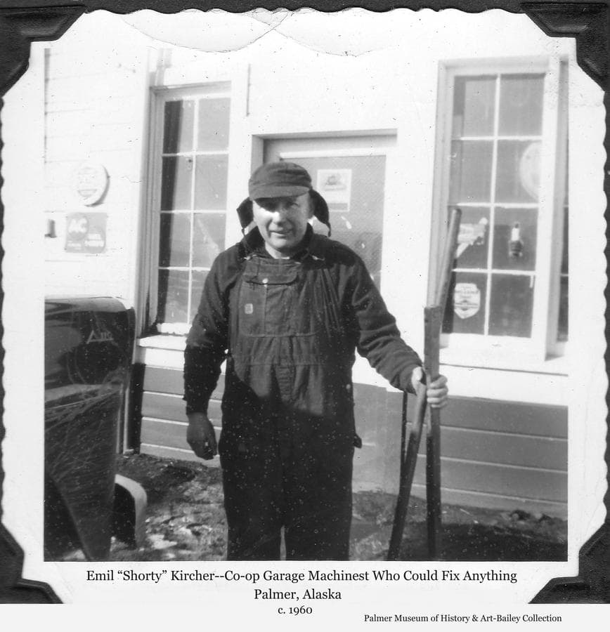 "Image is of a man, identified as Emil ""Shorty"" Kircher, standing in front of the Co-op Garage in Palmer.  ""Shorty"", as he was commonly known, was a German immigrant who, with his brother, acquired a homestead west of Palmer.  After the coming of the Matanuska Colony, he took a job as mechanic and machinist at the Co-op Garage and was known to be highly skilled and well regarded."