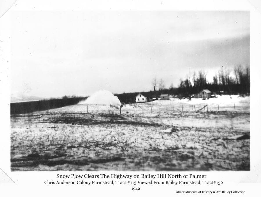 Image is a winter scene of the Chris Anderson Colony farmstead, tract #113, as viewed from the Bailey farmstead, tract #152.  A snow plow is visibly clearing snow from the main road leading north from Palmer as it crests Bailey Hill and passes between the two farms.