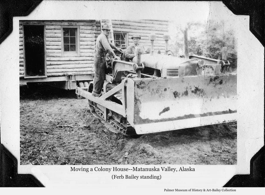 Image is of a log Colony house ready to be moved.  One man, identified as Ferber Bailey, stands on a caterpillar tractor while an unidentified man sits at the controls.  Support beams and wheels are visible under the house.  Over the years since the Matanuska Colony houses were constructed in 1935, many have been moved from their original locations as farms were consolidated and as housing was needed in Palmer or elsewhere throughout the valley.