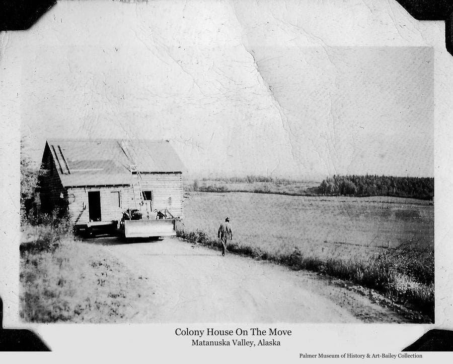 Image is of a log Colony house being pulled down the narrow road by a caterpillar tractor while a man, observing the progress, walks toward the house.  Fields and forest are visible in background. Over the years since the Matanuska Colony houses were constructed in 1935, many have been moved from their original locations as farms were consolidated and as housing was needed in Palmer or elsewhere throughout the valley.