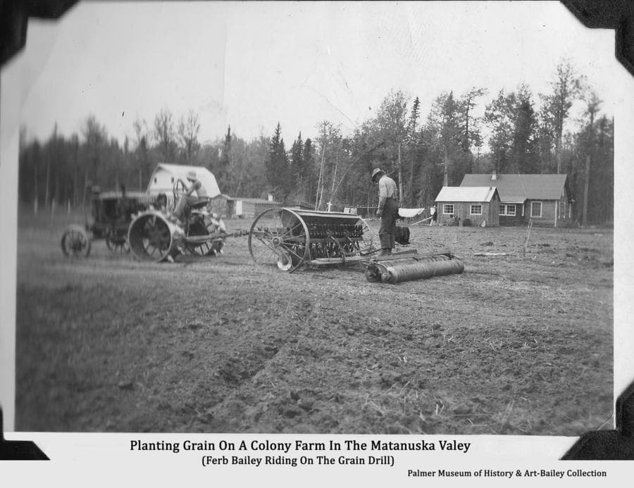 Image is of a Colony farmstead with a steel-wheeled tractor pulling a grain drill and cultipacker in the field in foreground.  A Colony house, barn and outbuildings are in the background.  One man is driving the tractor with another, identified as Ferber Bailey, riding on the packer behind the drill.