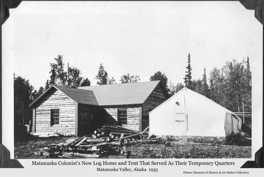 Image is of a newly-constructed Colony log home beside a Colony tent that furnished temporary quarters to the family while the house was being built.  Logs and lumber are in foreground and heavy forest is behind.