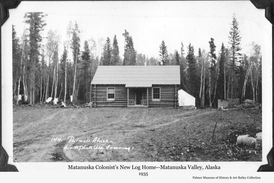 Image is of a newly-constructed Colony log home in a forest setting.  A Colony tent that furnished temporary quarters to the family while the house was being built is visible behind the house.   Cloths hang on a clothesline and heavy forest is close behind.