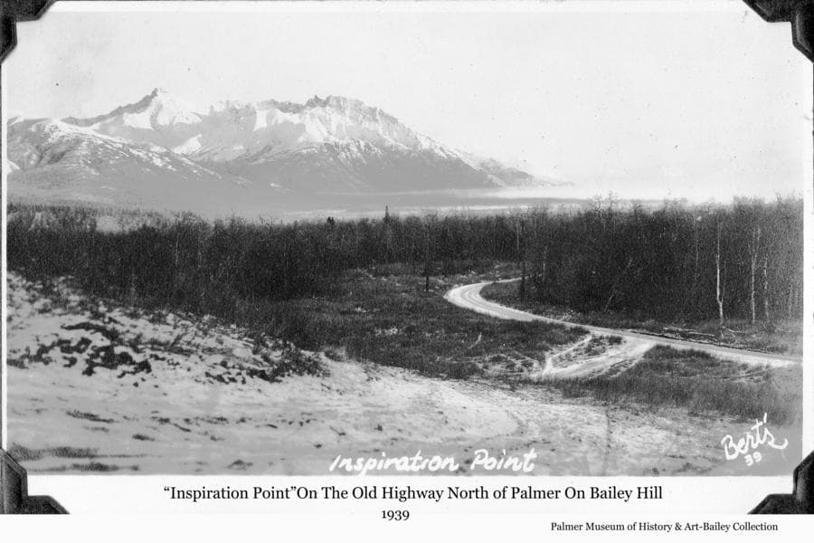 "Image is a southeasterly view from Bailey Hill, north of Palmer, toward the Knik River valley.   Chugach Mountains are in background.  Middle ground is heavy forest and a road section showing the curve in alignment necessary to ascend Bailey Hill, ultimately arriving at the point from which this photo was taken.  This was the only point on the road providing this expansive view of the Valley, thus the local name ""Inspiration Point"", and a popular stop for photographs. The road, which ultimately became Glenn Highway, was later straightened to cut through Bailey Hill, eliminating this section.  In foreground is a two-wheel dirt track showing where some drivers turned from the road to dive over the steep hill, cut across the field below, and arrive back at the road as visible in this picture, thus cutting off the longer route down the hill."
