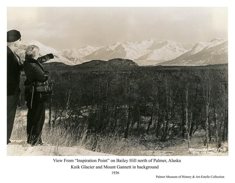 """Image is a southeasterly view from Bailey Hill, north of Palmer, toward the Knik River valley.   Chugach Mountains are in background.  Middle ground is heavy forest.  Barely visible through the trees is a road section before it curves in alignment necessary to ascend Bailey Hill, ultimately arriving at the point from which this photo was taken.  This was the only point on the road providing this expansive view of the Valley, thus the local name """"Inspiration Point"""", and a popular stop for photographs. The road, which ultimately became Glenn Highway, was later straightened to cut through Bailey Hill, eliminating public access to this favorite viewpoint."""