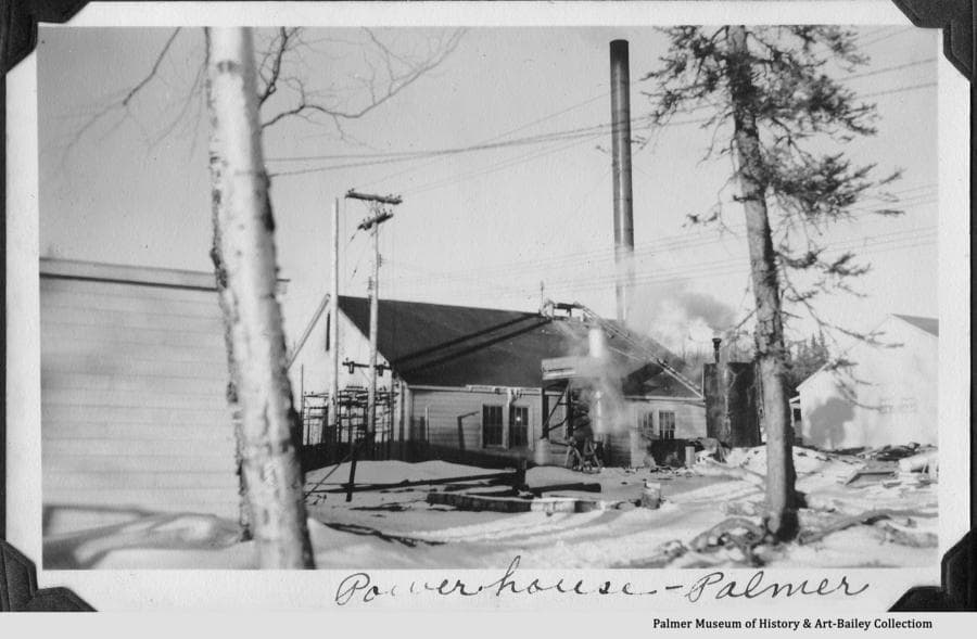 Image shows the powerhouse and part of the warehouse at right in the Palmer Community Center with snow on the ground.  Thought to be winter of 1935-36.