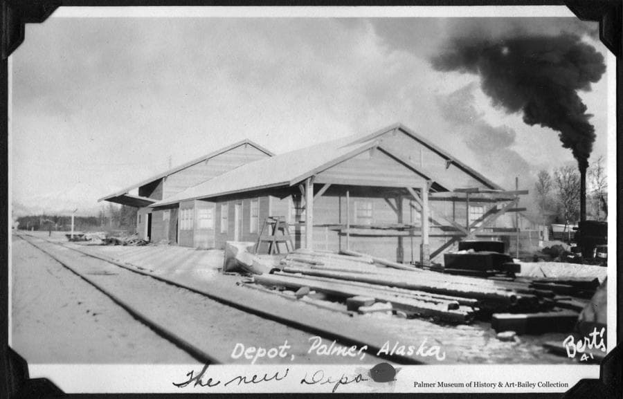 Image is a winter scene showing the southwest view of the Palmer railroad depot.  Exterior construction appears essentially complete but some scaffolding still in place and construction material still about.  Windows are covered on the inside possibly indicating interior work still in progress.  Photo probably taken winter of 1936-37.  Black smoke issues from an unidentified smoke stack.