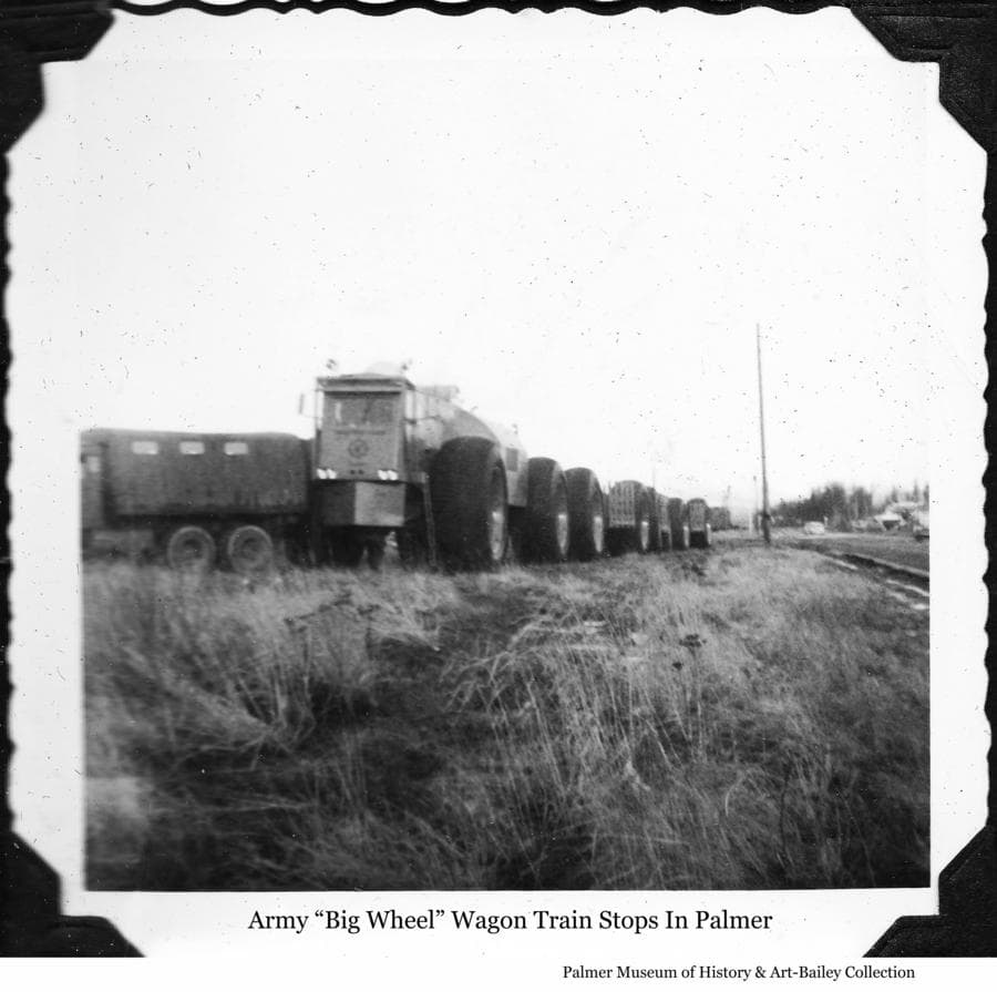 "Image is of an Army ""Big Wheel"" overland train parked beside the railroad track in downtown Palmer.  An Army truck is backed up to the cab of the train.  The date is yet to be determined."