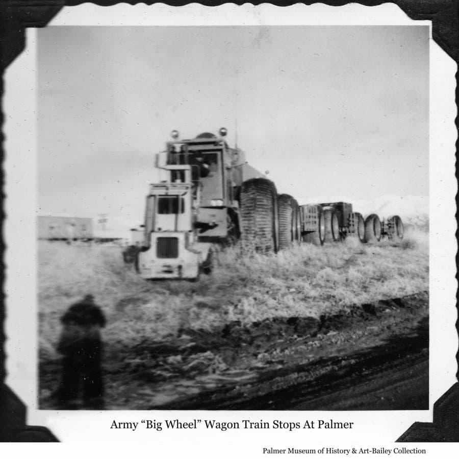 "Image is of an Army ""Big Wheel"" overland train parked beside the railroad track in downtown Palmer.  A fork lift is in front of the vehicle's cab and appears to be lifting a man up to clean the cab's windows.  The date is yet to be determined."