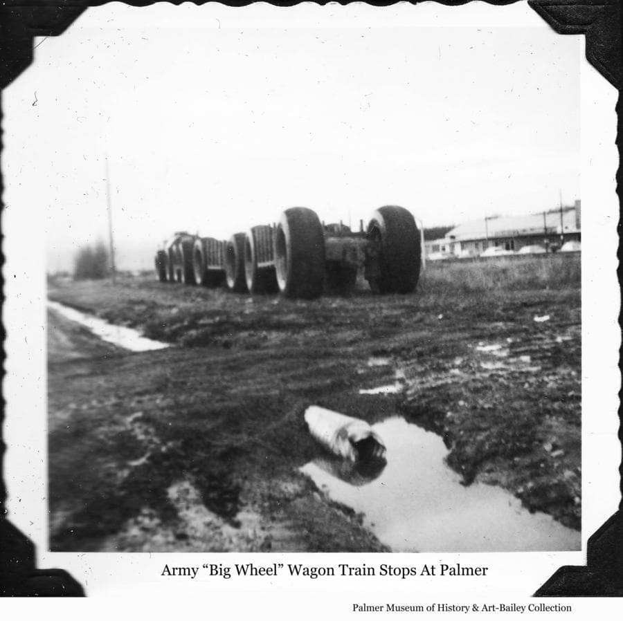 "Image is of an Army ""Big Wheel"" overland train parked beside the railroad track in downtown Palmer.  The theater building is visible beyond the railroad tracks to the right.  Date of the photo is yet to be determined."
