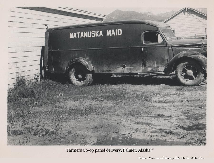 Image is a summer view of a panel truck with MATANUSKA MAID lettered on the side, parked next to a building with Lazy Mountain visible in background.