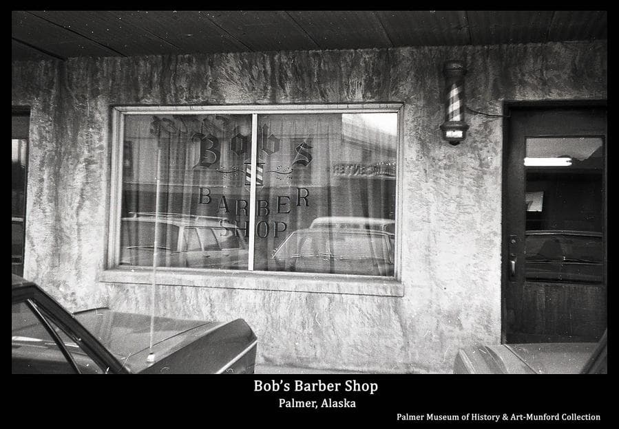 Image is a summer street view of the entrance to Bob's Barber Shop located in the Wright Building facing W. Elmwood Ave.  The shop sign is painted on the window and an electric barber pole is evident.  The Center Theater and Palmer Laundry across the street are reflected in the window.