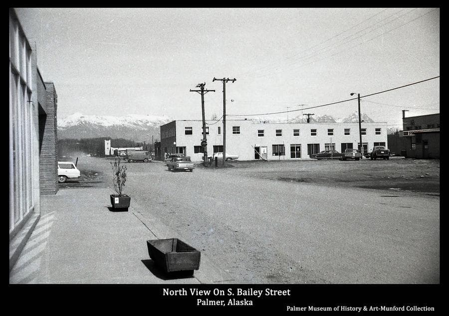 Image is a summer street view on South Bailey Street looking north from the Post Office at the Severns Building in middle ground, the First Baptist Church in far middle ground, and snow-capped mountains in background.