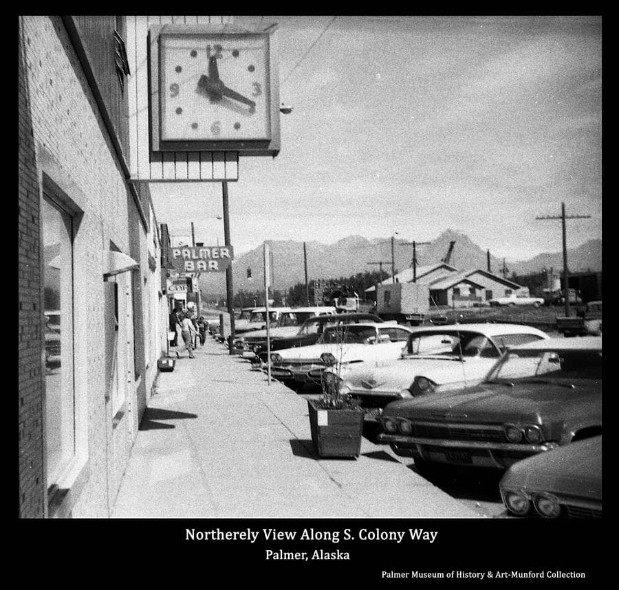 Image is a summer street view on South Colony Way looking north from the sidewalk in front of the Matanuska Valley Bank.  The bank clock is apparent in foreground and other business signs are evident.  Cars are parked at the curb, people are on the sidewalk in middle ground.  The depot is visible and Talkeetns Mountains form the background.