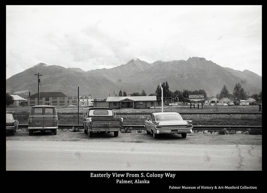Image is a summer street view on South Colony Way looking to the east.  The view includes the Palmer Visitor Center, School, Dorm, MEA Building, and Houses, with Mountains in background.  Automobiles are parked in foreground.