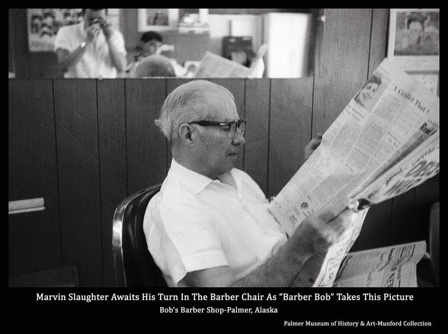 Marvin Slaughter sits reading a newspaper as he awaits his turn in the barber chair for a haircut.  Bob Munford can be seen in the mirror above taking this picture.