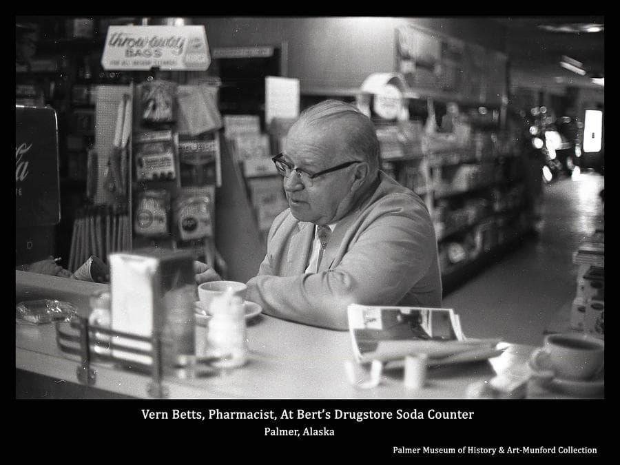 Image is of Vern Betts, pharmacist at Bert's Drugstore, taking a coffee break at the drugstore soda counter.  The hallway behind leads to the front door on S. Colony Way past shelves and display counters filled to overflowing with about anything a Valley resident might be tempted to buy.