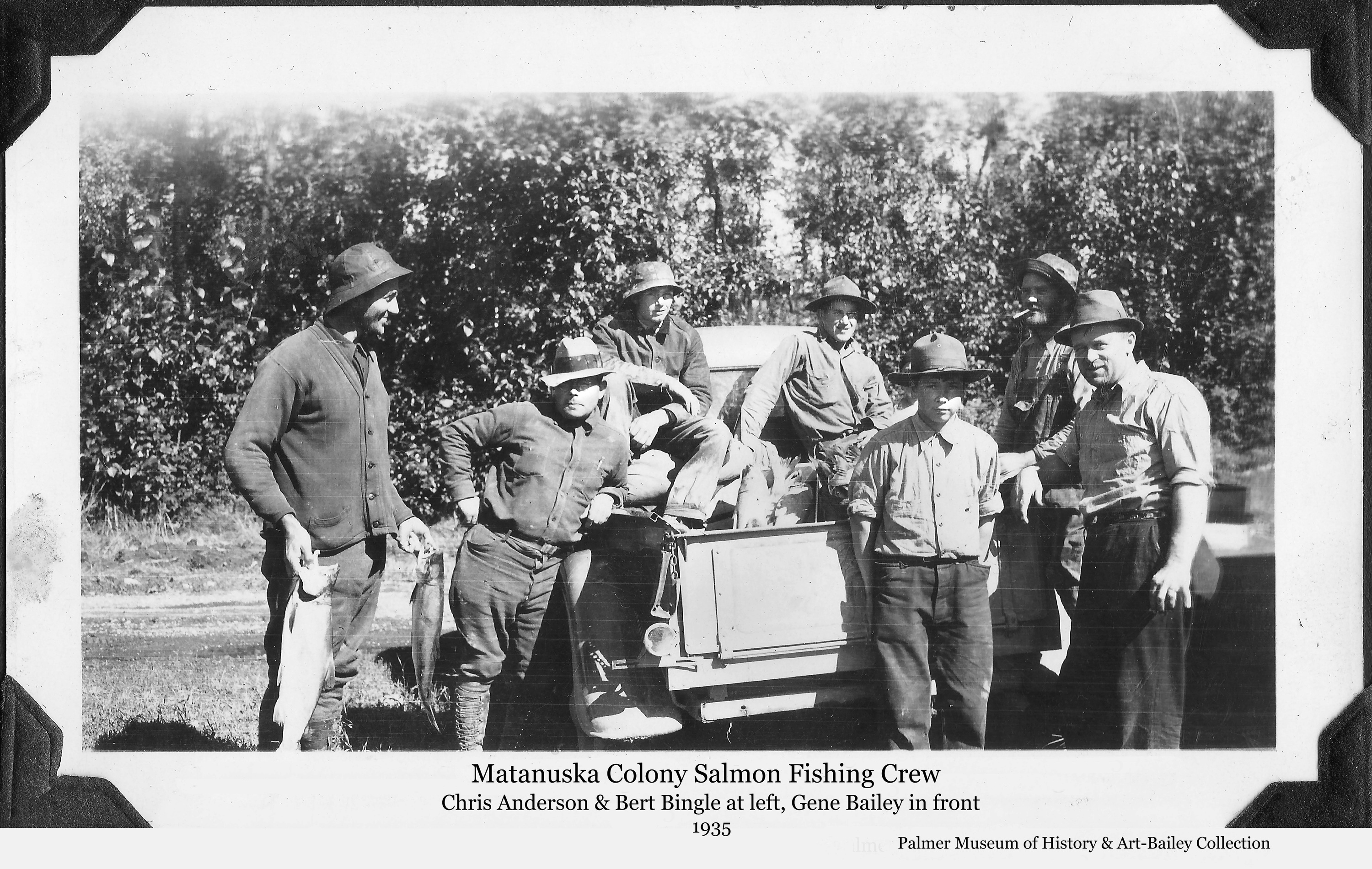 Image is a summer view of seven men gathered around the back of a pickup truck.   A man at left, identified as Colonist Chris Anderson, is holding two salmon in his hands.  Additional salmon are visible in the back of the truck.  Rev. Bert Bingle leans against the truck next to Anderson.  Young Gene Bailey stands front and center.
