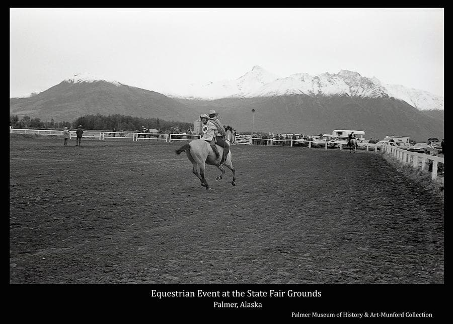 Image is of a horse and two riders in the arena at the State Fairgrounds in Palmer.  People, horses and vehicles are evident outside the arena fence.  Chugach Mountains, capped with snow, are in background.