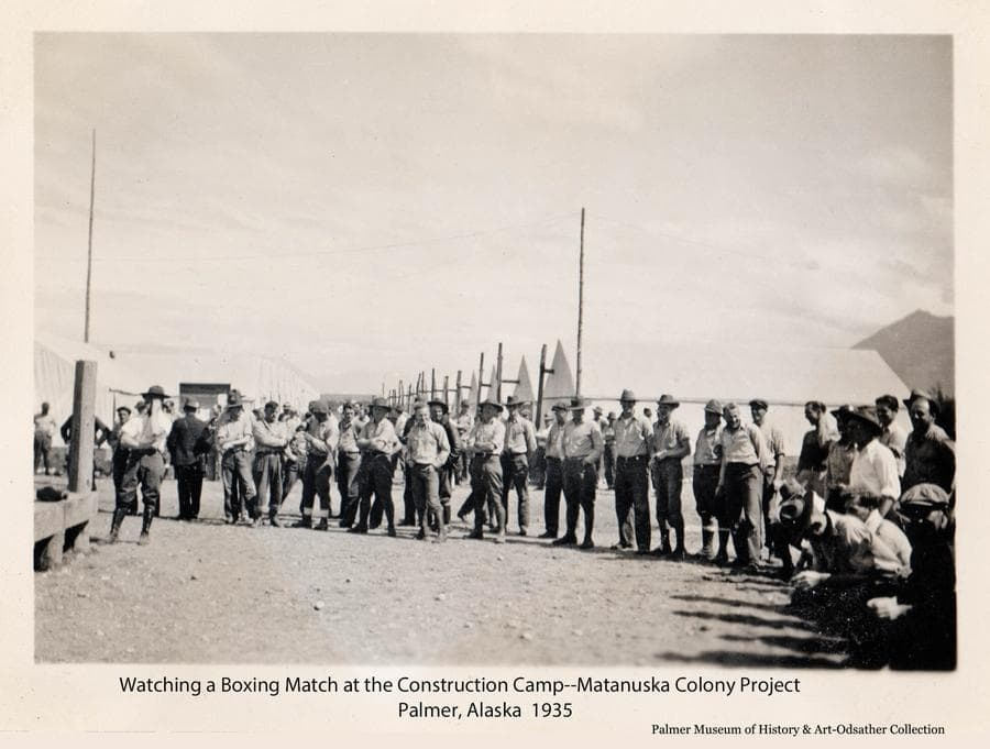 Image is of a group of men gathered at the Matanuska Colony construction camp, said to be watching a boxing match off camera.  Tents of the camp are visible in background.