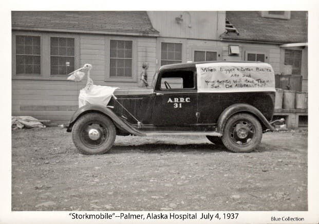 """Image shows the Palmer Hospital's """"Nurses Car"""" and community ambulance decorated for the Palmer 1937 4th-of-July parade. On the front is a white stork figure holding a baby basket in its beak. The car's back panel is covered with a white sheet with lettering proclaiming """"When Bigger & Better Babies are had, Your Hospital Will Have Them!! See Dr. Albrecht!!!?"""" The vehicle has ARRC 31 printed in white on the side of the door. The rear of the hospital is behind the vehicle with garbage cans in evidence. A woman (probably a nurse) walks behind the vehicle."""