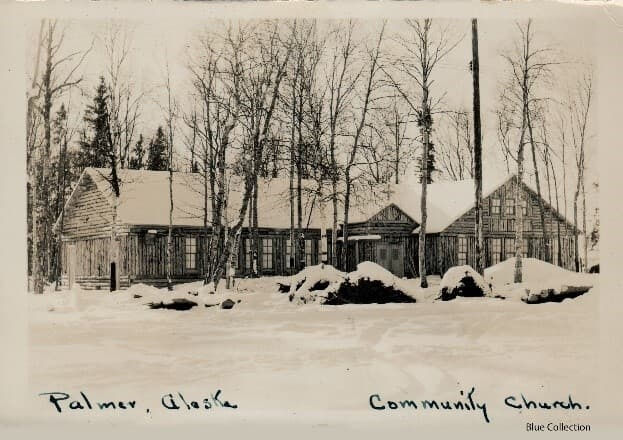 Image shows the north side of the Palmer Protestant Church in winter with trees in the foreground and background and with snow all over. A power pole and power lines are in the foreground. This photo is printed on a postcard, but has no attribution to a photographer.