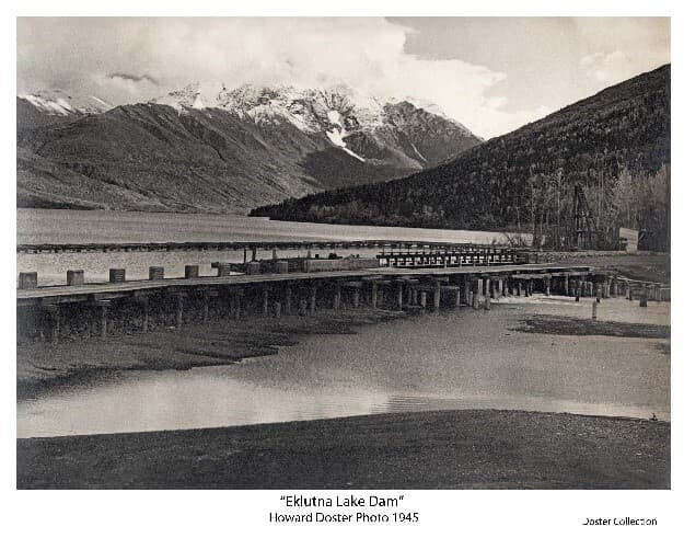 Image shows the lower side of Eklutna Lake Dam with the lake and mountains beyond. The spillway is evident with water flowing into the outlet river. A wooden pole tower is visible at the right extent of the dam near a small shed. A second horizontal structure on pilings is visible in the lake behind the dam.