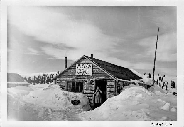 """Image shows a winter view of a log building approximately 15' x 30' in size with snow piled around it. A woman in an apron stands in the open doorway smoking a cigarette. A large sign on the exterior gable end wall reads: """"EUREKA ROAD HOUSE MEALS LUNCHES OIL-GAS"""". A smaller sign on the wall between the door and window advertises """"Rainier Pale Special Export Beer"""". Two chimney pipes are visible as is a tall antenna pole and wire. Another building (tent?) is partially visible to the side. Snow covered hills and evergreen trees are apparent in background."""